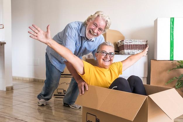 Das glück von zwei senioren im leeren raum, die wie kinder beim umzug spielen, glücklich über einen neuanfang wie im ruhestand mit umzugskartons auf dem boden
