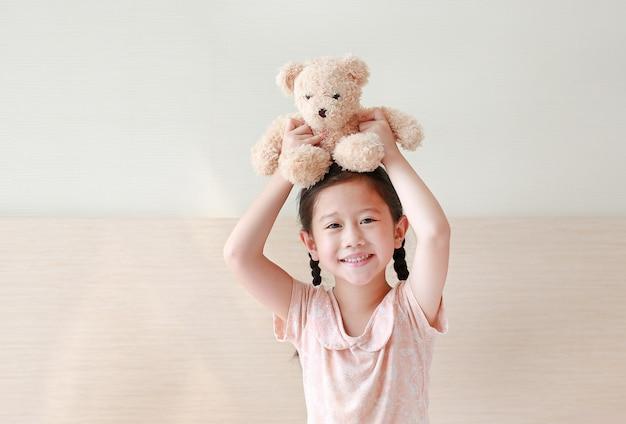 Das glückliche asiatische kleine mädchen, das braunen teddybären aufhebt, betrifft ihren kopf beim auf dem bett zu hause sitzen