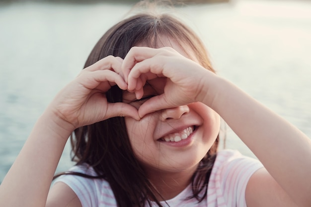 Das glückliche asiatische mädchen, das ein herz macht, formen mit ihren händen für herzgesundheit und das geben des spendenkonzeptes