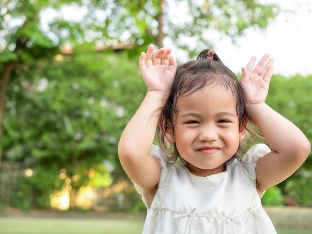 Das glückliche asiatische nette lächelnde baby und machen reizende aktion und täuschen vor, katze oder kaninchen im park nachzuahmen.