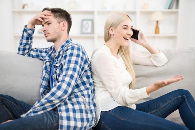 Das glückliche frauentelefon neben einem mann auf dem sofa