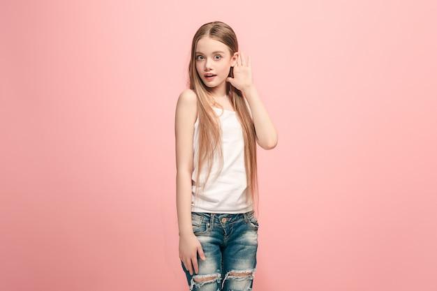 Das glückliche jugendlich mädchen, das auf trendigem rosa studio steht und zuhört