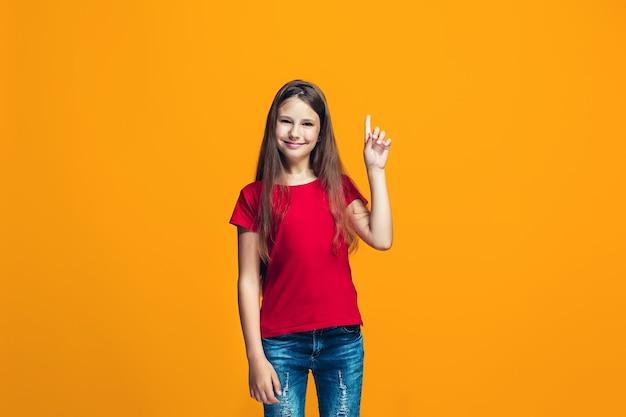 Das glückliche jugendlich mädchen, das gegen orange steht und lächelt.