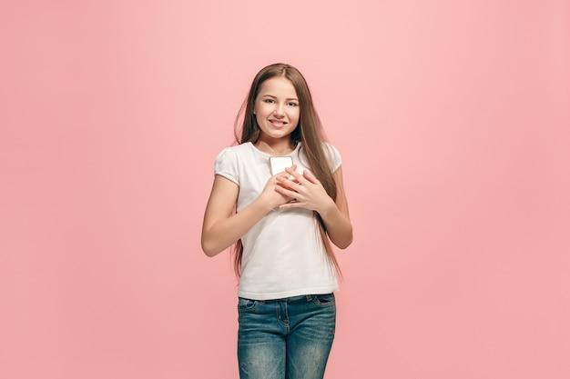 Das glückliche jugendlich mädchen mit dem telefon, das gegen rosa wand steht und lächelt