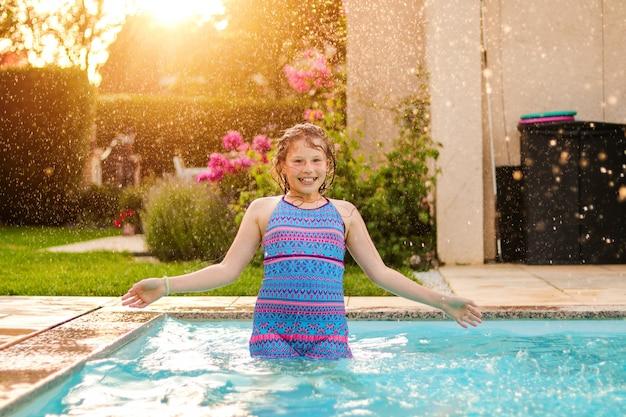 Das glückliche jugendliche mädchen, das spaß im swimmingpool unter regenwasser hat, fällt draußen in garten bei sonnenuntergang.