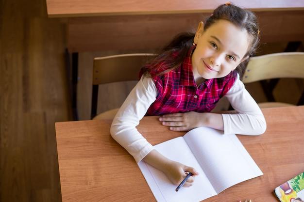 Das glückliche kaukasische mädchen, das am schreibtisch im klassenzimmer sitzt und fängt an, in ein reines notizbuch zu zeichnen.