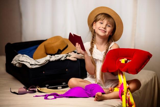 Das glückliche kindermädchen des reisekonzepts mit einem koffer und einem reisepass bereitet für urlaubsreise freude und glück ein lächeln auf ihrem gesicht vor
