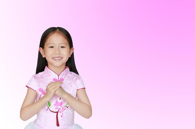 Das glückliche kleine asiatische kindermädchen, das rosa kleid des traditionellen chinesen mit grußgestenfeier trägt