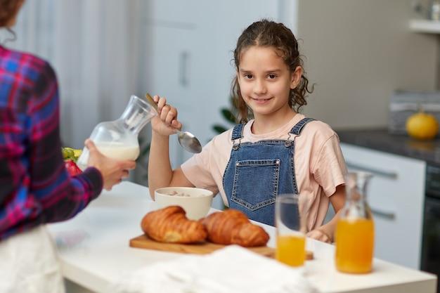 Das glückliche kleine mädchen, das die kamera beim gesunden frühstück zusammen mit der mutter in der küche betrachtet.