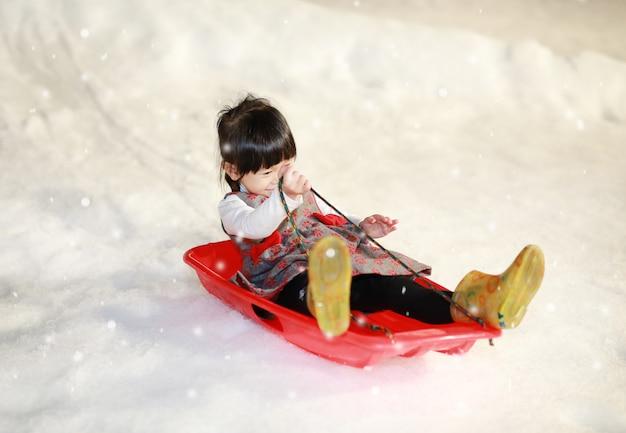 Das glückliche kleine mädchen, das eine rot - graue jacke trägt, hat spaß im schnee