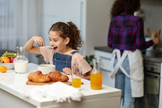 Das glückliche kleine mädchen, das zusammen mit der mutter in der küche gesundes frühstück des getreides isst.