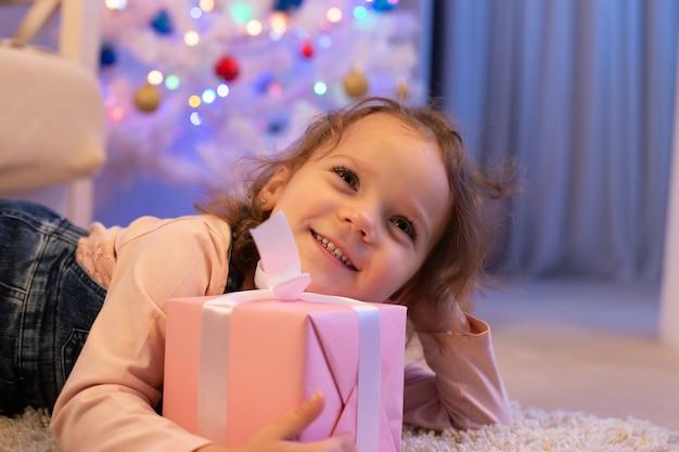 Das glückliche kleine mädchen mit einem geschenk an weihnachten