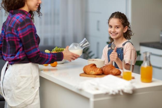 Das glückliche kleine mädchen zeigt die daumen beim gesunden frühstück zusammen mit der mutter in der küche.
