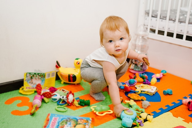 Das glückliche kleine mädchen zeigt und spielt viele spielsachen auf farbigen matten und puzzles