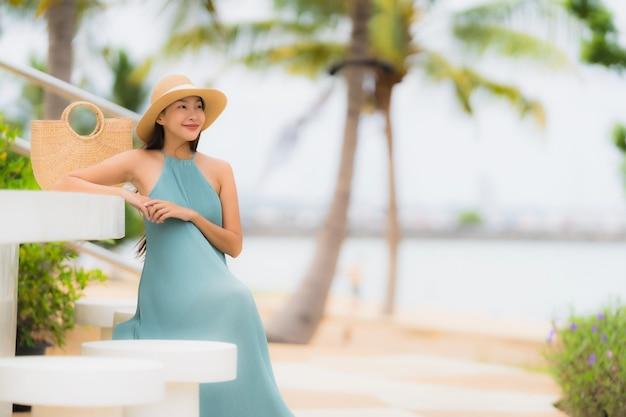 Das glückliche lächeln der jungen asiatischen frauen des schönen porträts entspannen sich um strandseeozean