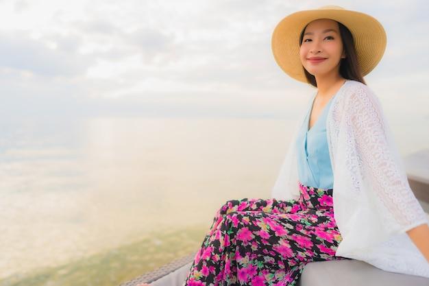 Das glückliche lächeln der schönen jungen asiatischen frauen des porträts entspannen sich um seestrandozean