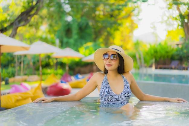 Das glückliche lächeln der schönen jungen asiatischen frauen entspannt sich um den außenpool im hotelresort für reisen im urlaub
