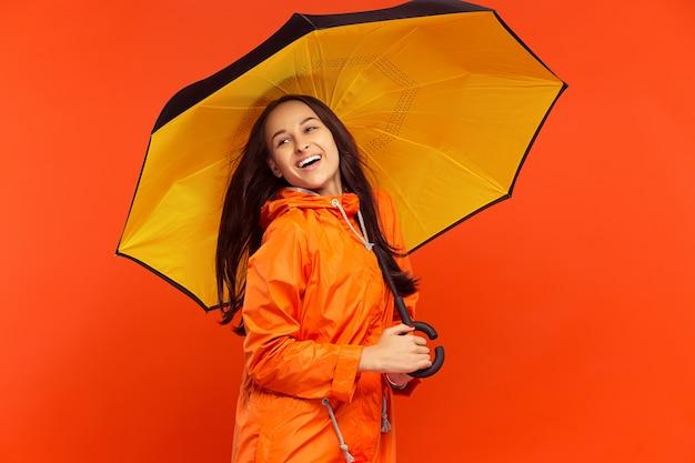 Das glückliche lächelnde junge mädchen, das im studio in der orangefarbenen herbstjacke auf orange wand lokalisiert aufwirft