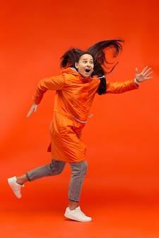 Das glückliche lächelnde junge mädchen, das im studio in der orangefarbenen herbstjacke auf rot aufwirft.