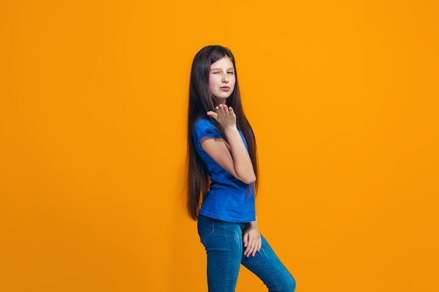 Das glückliche mädchen, das gegen orange wand steht und lächelt