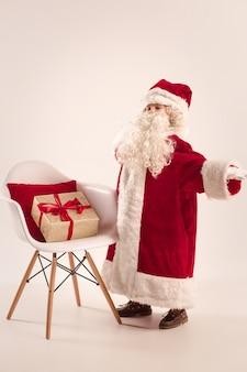 Das glückliche mädchen im weihnachtsmannkostüm mit geschenkbox im studio. kleines jugendliches kaukasisches modell. das weihnachts-, feiertagskonzept