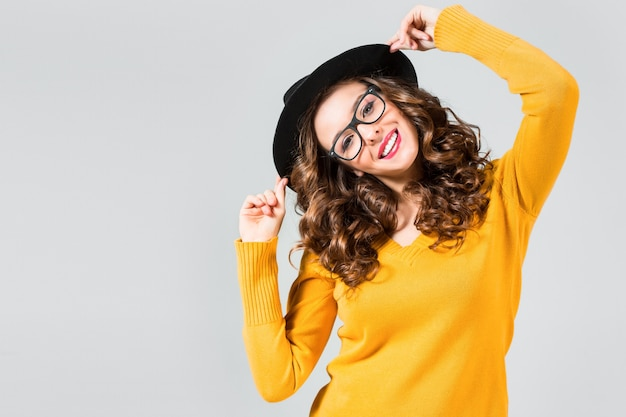 Das glückliche mädchen mit brille und hut auf grauer studiooberfläche