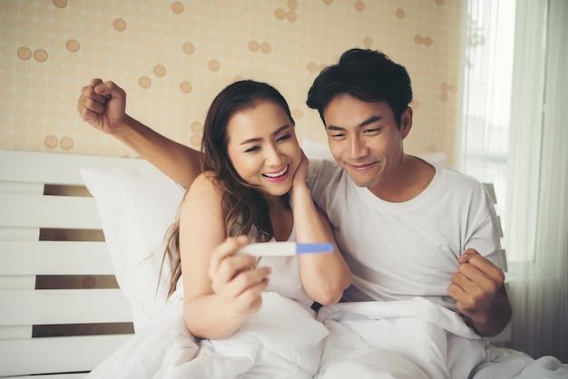 Das glückliche paar, das nach lächelt, finden positiven schwangerschaftstest im schlafzimmer heraus