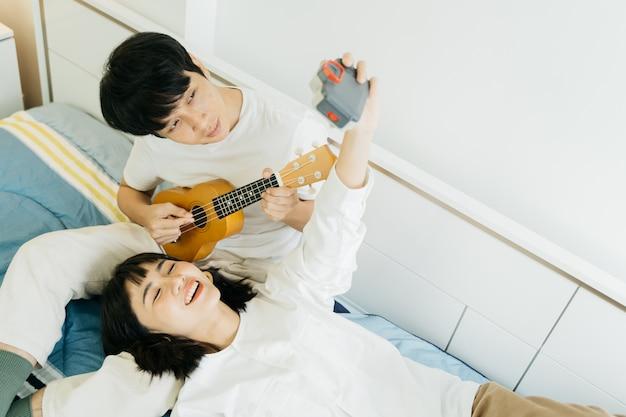 Das glückliche paar, das ukulele spielt und machen ein foto selbst