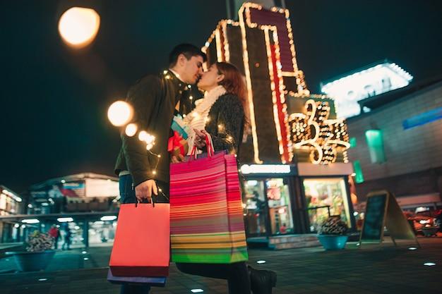 Das glückliche paar mit einkaufstüten genießt die nacht im stadthintergrund und geht mit einkaufstüten. lebensstil.