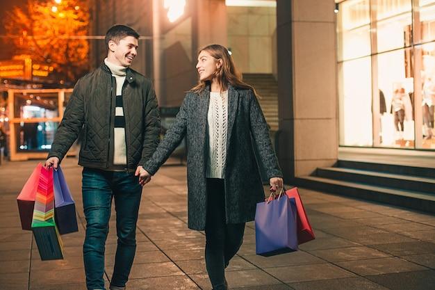 Das glückliche paar mit einkaufstüten genießt die nacht in der stadt