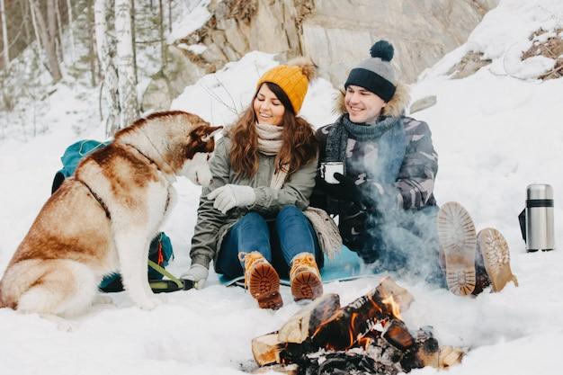 Das glückliche paar mit hund haski am waldnaturpark in der kalten jahreszeit