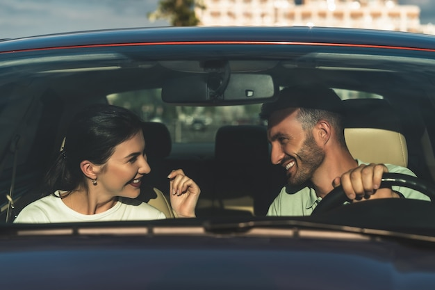 Das glückliche paar sitzt im auto