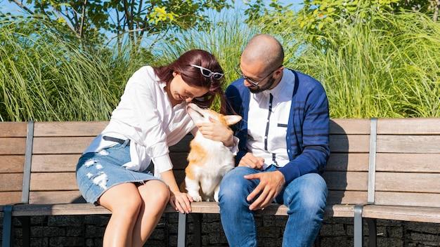 Das glückliche paar sitzt mit dem kleinen hund corgi pembroke auf der bank im park.