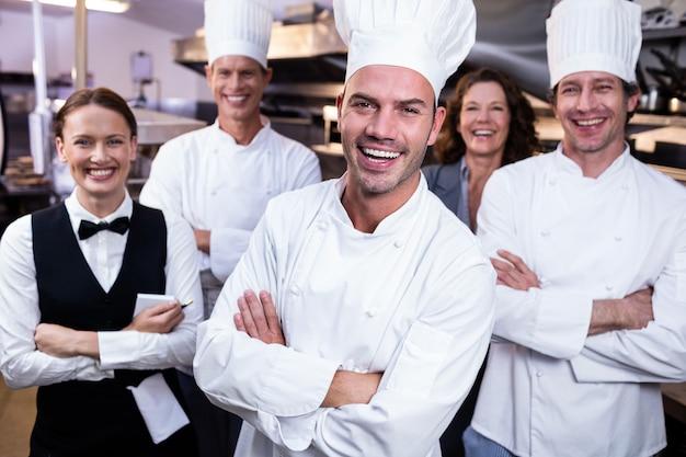 Das glückliche restaurantteam, das zusammen mit den armen steht, kreuzte in der handelsküche
