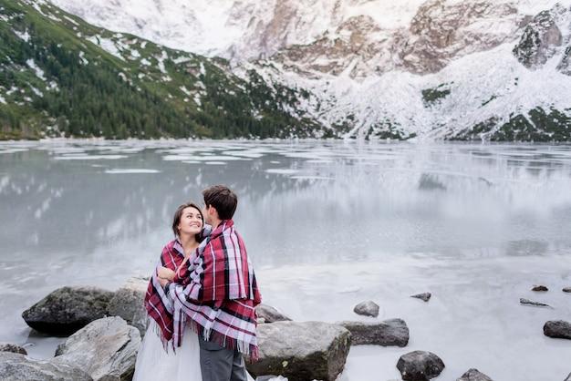 Das glückliche verliebte paar schaut sich vor der atemberaubenden wintergebirgslandschaft und dem zugefrorenen see tatry mountains an