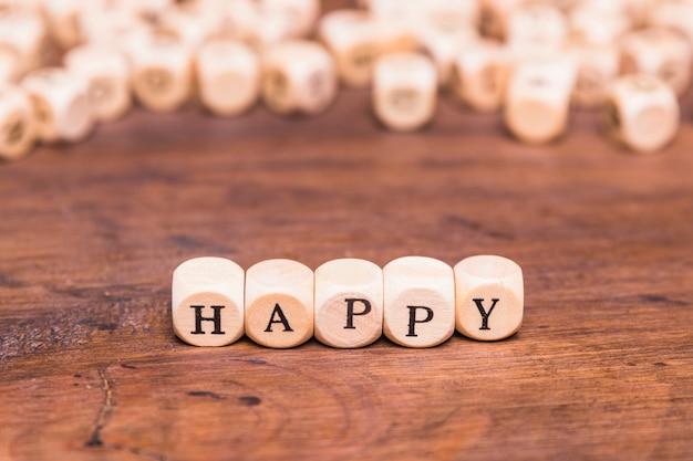 Das glückliche wort, das auf würfel geschrieben wird, formen holzklötze