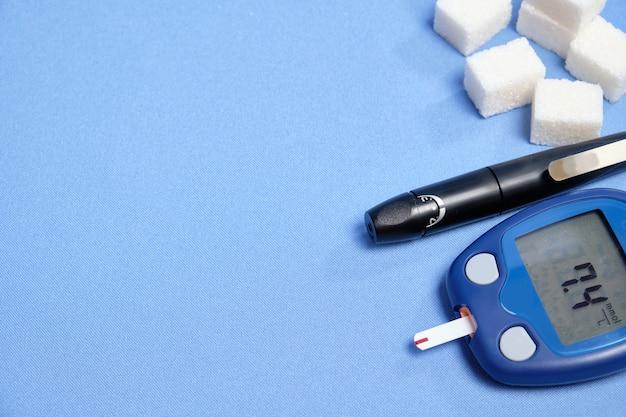 Das glukometer mit dem teststreifen auf einem blauen raum. platz für text, selektiver fokus