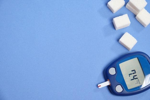 Das glukometer mit dem teststreifen auf einem blauen raum. platz für text