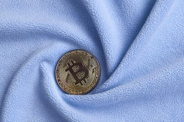 Das goldene bitcoin liegt auf einer decke aus weichem und flauschigem hellblauem fleece