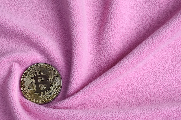 Das goldene bitcoin liegt auf einer decke aus weichem und flauschigem hellrosa fleece