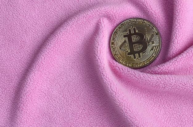 Das goldene bitcoin liegt auf einer decke aus weichem und flauschigem stoff