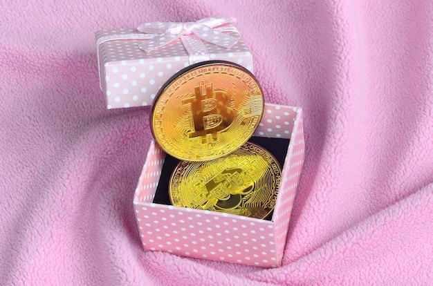 Das goldene bitcoin liegt in einer kleinen rosa geschenkbox mit einer kleinen schleife auf einer decke