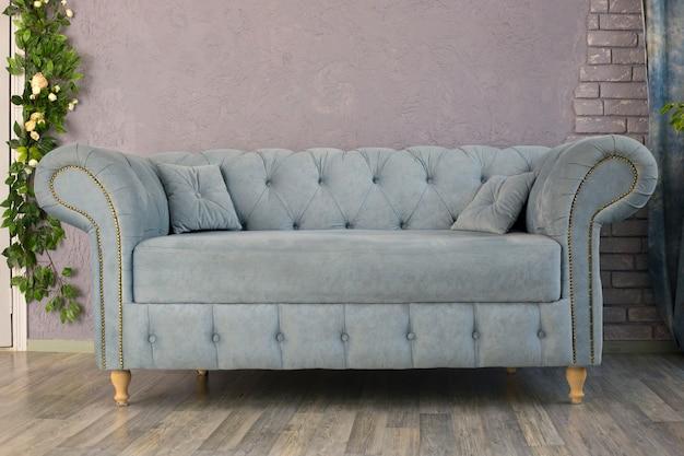 Das graublaue sofa steht in der nähe der grauen wand im raum. innenarchitektur
