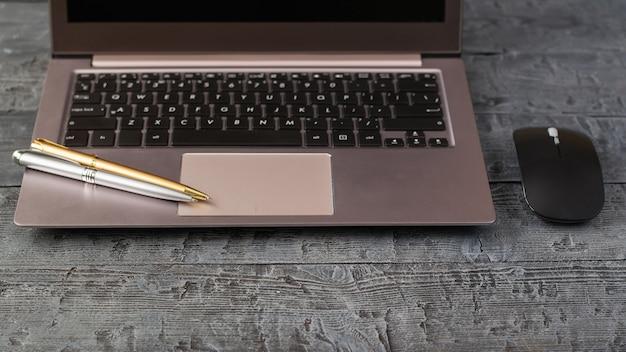 Das graue notizbuch und zwei kugelschreiber auf weinleseholztisch. arbeitsplatzdesigner.