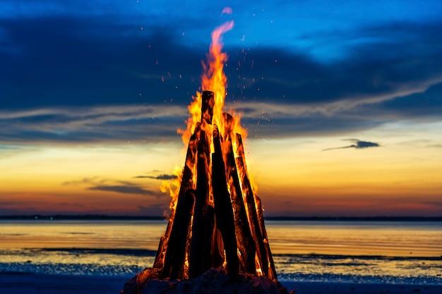 Das große feuer brennt vor dem hintergrund des nachthimmels, ganz nah