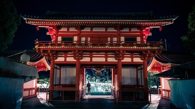 Das große tor und eingangsgebäude des yasaka jinja schreins mit besuchern in der nacht. der gion-tempel ist einer der berühmtesten schreine in kyoto