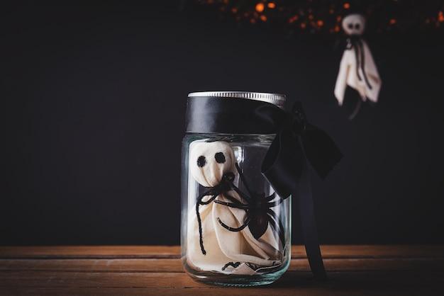 Das gruselige gesicht des weißen geistes und die schwarze spinne im glas auf holztisch