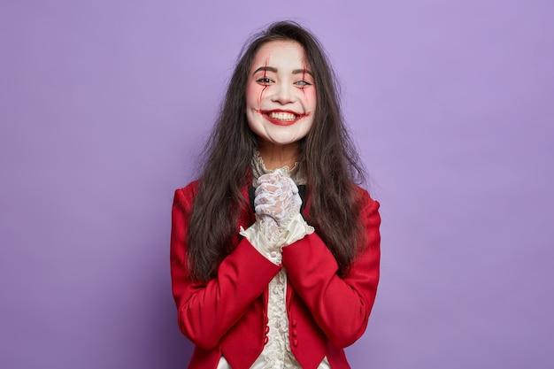 Das gruselige halloween-mädchen mit dem gruseligen make-up-lächeln freut sich auf die maskerade-party und hält die hände auf der lila wand isoliert zusammen. blutige gesichtskunst