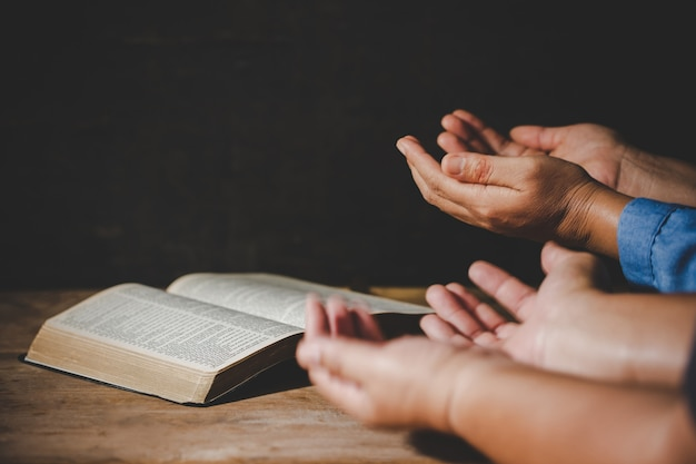 Das händchenhalten der gruppe von personen, das anbetung betet, glauben