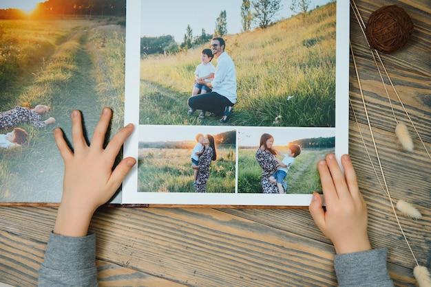 Das handkind, das ein familienfotoalbum eines holztischs hält